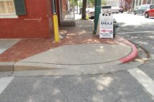 Non-compliant perpendicular ramps with signal pole, bollard and hydrant